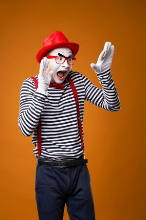 Frightened mime man in vest and red hat on orange background.