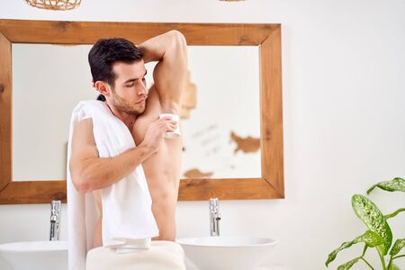 Young male applies deodorant to armpits while standing in bath opposite mirror Banque d'images