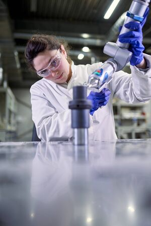 Young woman lab technician in blue rubber gloves with 3D printer on defocused background