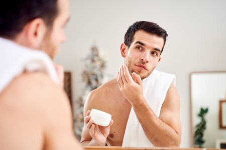 Brunet male with towel on his shoulders with jar of cream in his hands stands in front of bathroom mirror Stock Photo