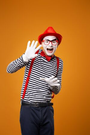 Happy mime man looking at camera in vest and red hat Isolated on orange background