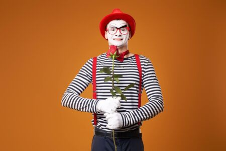 Smiling mime in red hat, glasses and vest with rose in hands on empty orange background