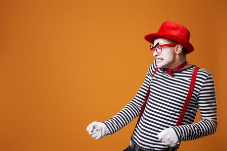 Evil mime in vest and red hat on orange empty background