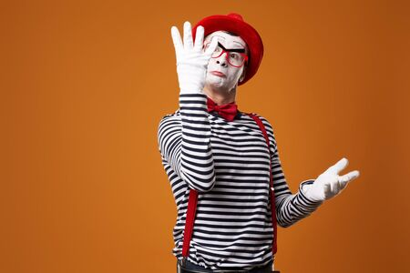 Serious mime male in vest and red hat with raised palms on orange background