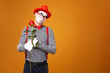 Pensive mime with white face in red hat and striped t-shirt holding rose isolated on empty orange background