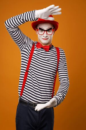Smiling mime with white face in red hat and striped t-shirt on blank orange background Banco de Imagens