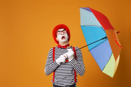 Mime looking up with multi-colored umbrella isolated on empty orange background