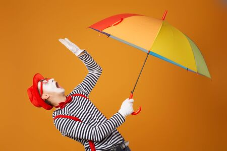 Sad mime man looking up with multi-colored umbrella in hand isolated on blank orange background in studio Banco de Imagens - 139706189