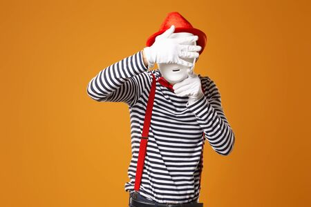 Mime in red hat and in vest with white mask on blank orange background