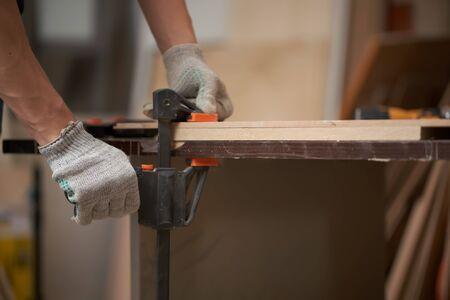 Man carpenter clamps board in vice in workshop