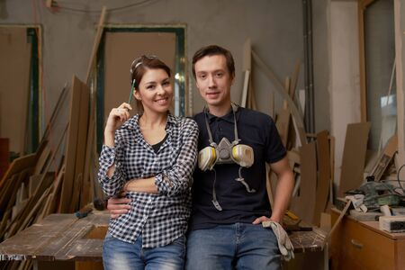 Young couple joiners sitting in workshop