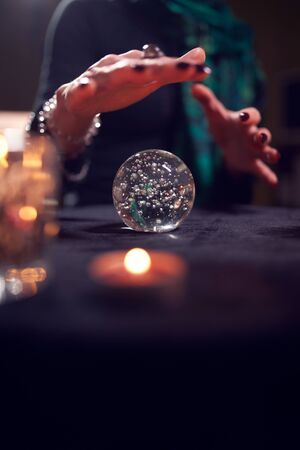 Close-up of female fortune-teller's hands with ball of predictions in dark room