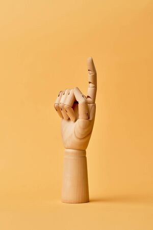 Wooden human hand with one finger up on empty orange background