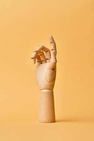 Wooden hand isolated on orange background, close up