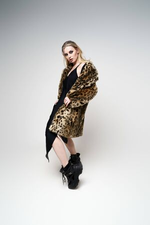 Blonde woman in leopard coat and boots looking at side while standing in studio Stock Photo