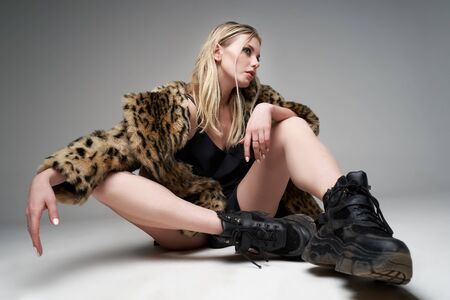 Young blonde girl in leopard coat and boots looking at side while sitting in studio, Stock Photo