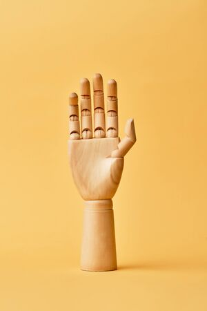 One wooden mannequin hand raised up