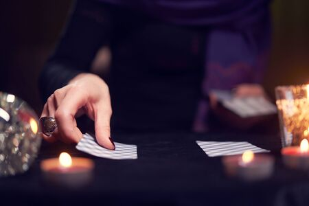 Close-up of fortunetellers hands with fortune-telling cards at table with candles