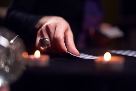 Close-up of woman fortunetellers hands with fortune-telling cards at table with candles Banque d'images