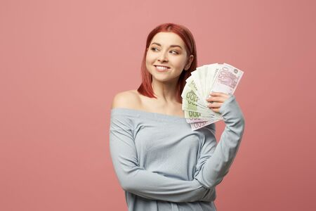 Smiling woman holding euro banknotes in hands while standing in studio 版權商用圖片