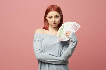 Young woman holding euro banknotes in hands while standing in studio 版權商用圖片