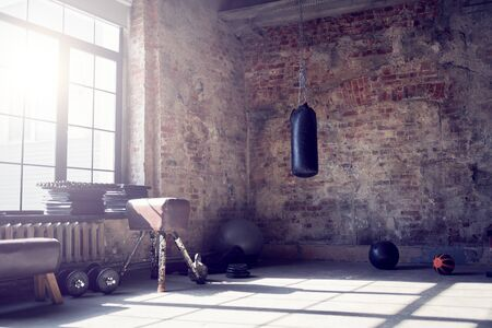 Gym with brick wall with sports equipment, light from window