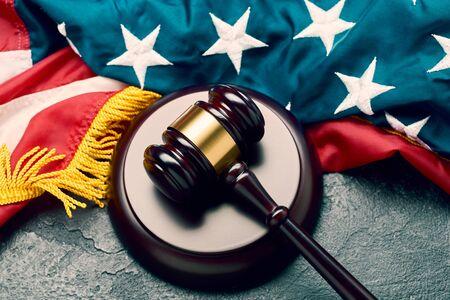 Judges wooden gavel on background of American flag on black background