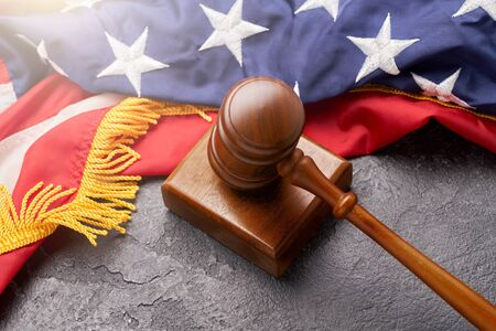 Top view of wooden judge gavel against background of American flag on black surface