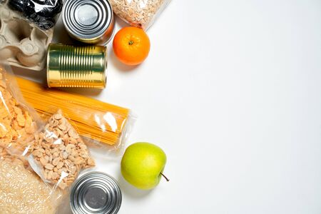 Various foods sealed in plastic bags, cans and fruits on white background, top view.