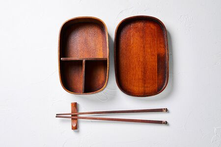 Open wooden bento box. with wooden sticks.