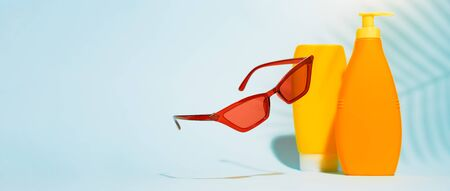 Two orange containers without label for lotion, red glasses on blue background