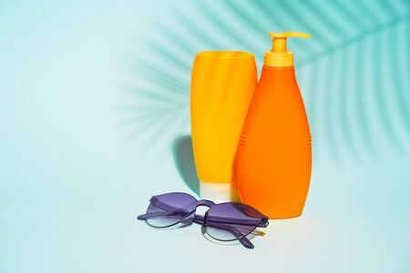 Orange containers without label for lotion, purple sunglasses on blue background, space for text