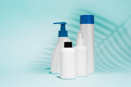 White containers for spray, liquid soap on clean blue background, close up