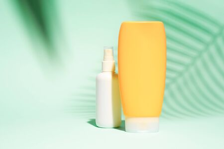 White and orange spray containers without label on turquoise background, place for text