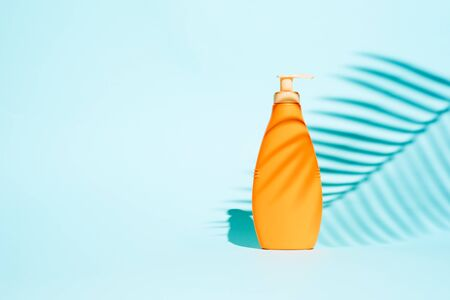 Orange container for lotion without label on blue background with leaf