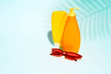Two orange containers without label for lotion, red glasses 版權商用圖片