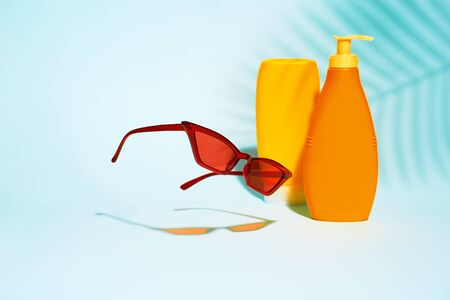 Two orange containers without label for lotion, sunglasses on blue background 版權商用圖片