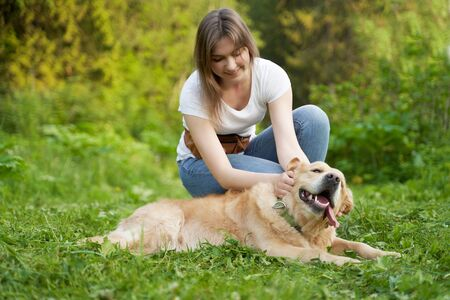 Young woman squatting next to dog while walking