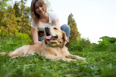 Happy woman squatting next to dog while walking 版權商用圖片