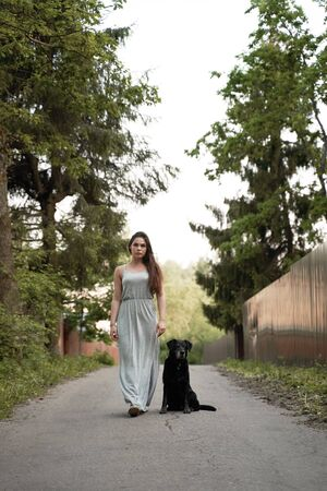 Brunette woman on walk with black dog in park on summer