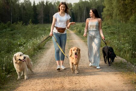 Two young women on walk with three dogs in park