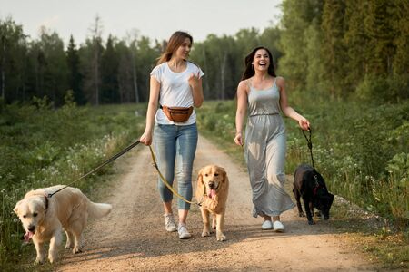 Two happy women on walk with three dogs in park