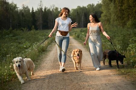 Happy women on walk with three dogs in park