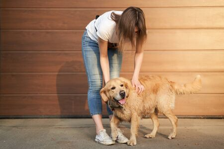 Woman in blue jeans stroking dog outdoors in afternoon against brown wall 版權商用圖片