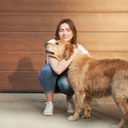 Woman in blue jeans hugging dog outdoors in afternoon .