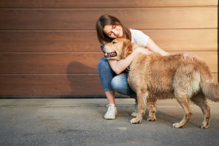 Happy girl in blue jeans hugging dog outdoors in afternoon 版權商用圖片