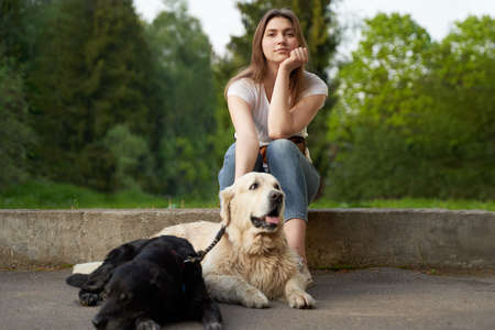 Pensive woman squatting next to dog on summer day.