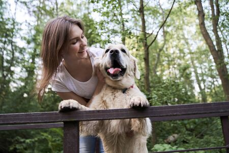 Happy woman with labrador standing on bridge among forest on summer day