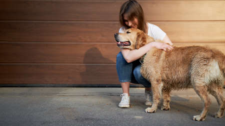 Happy woman in blue jeans hugging dog outdoors in afternoon