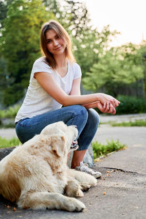 Cheerful girl in jeans on walk with retriever on summer